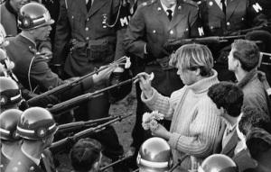 George Harris sticks carnations in gun barrels during an antiwar demonstration at the Pentagon in 1967. (By Bernie Boston -- The Washington Evening Star)